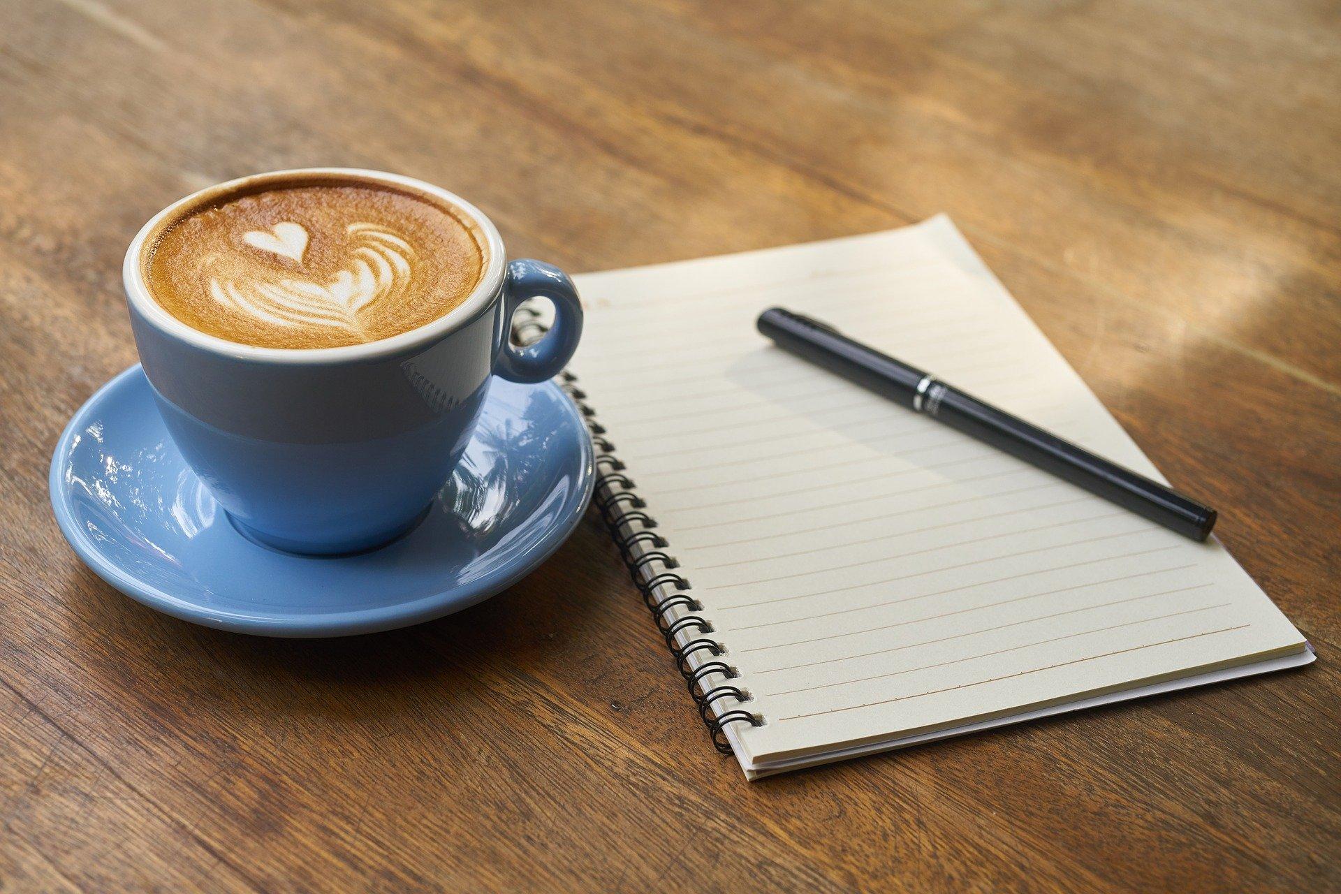 Ein Holztisch mit einer Tasse Kaffee und einem Schreibblock mit Stift.