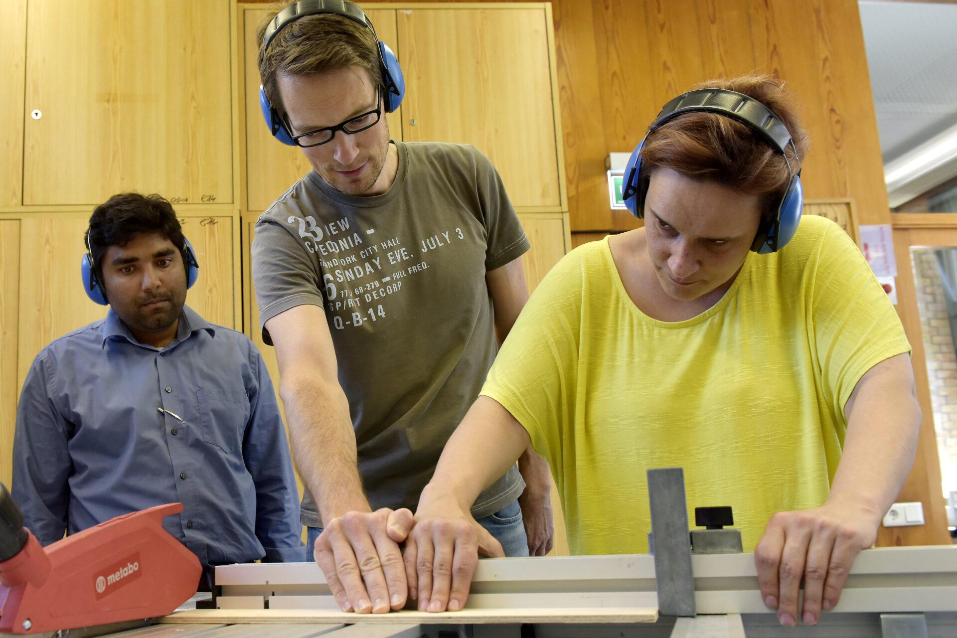 Das Bild zeigt 2 Auszubildende, eine Frau und ein Mann, mit einem Ausbilder an einer Holzwerkbank