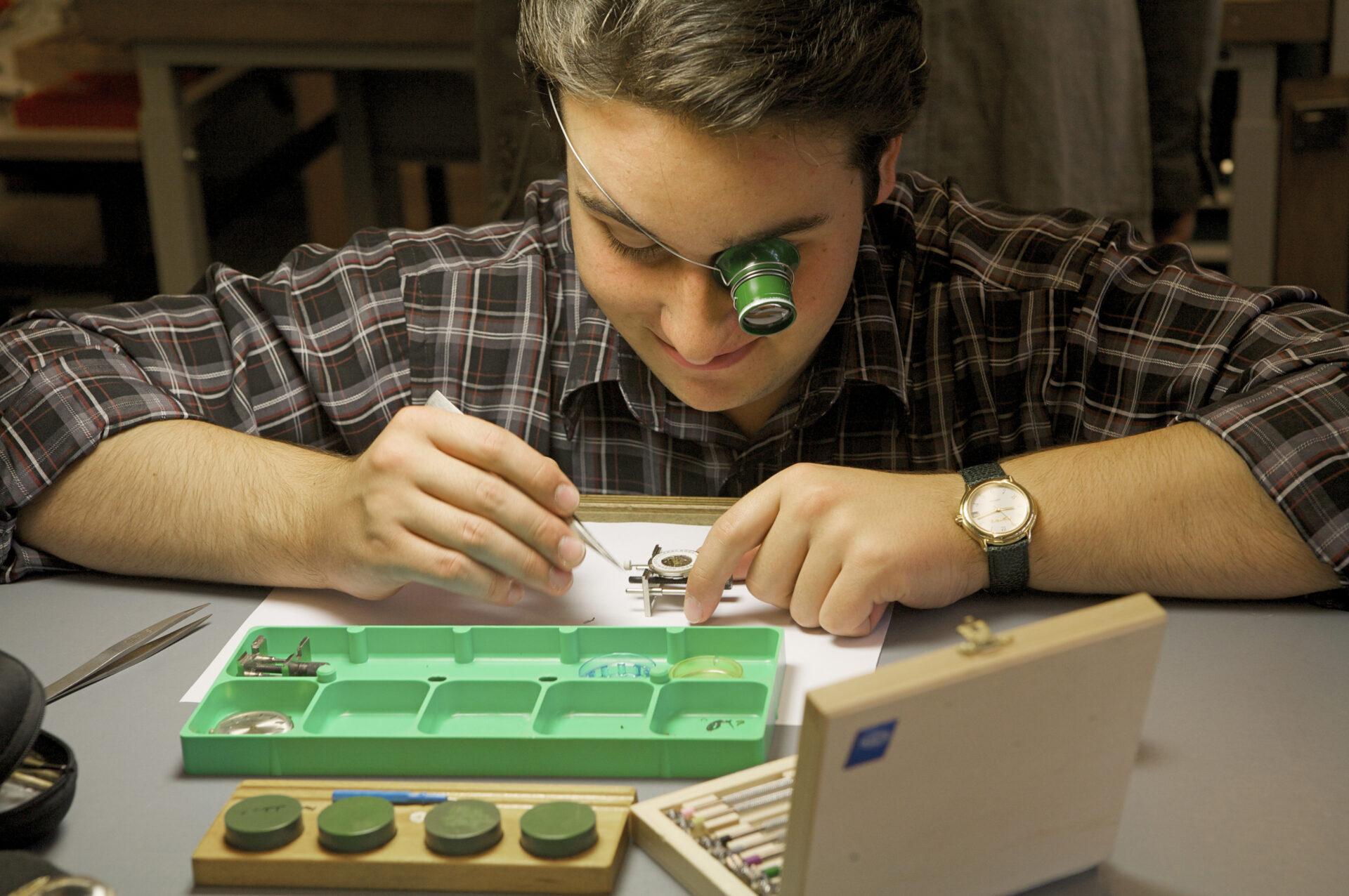 das Foto zeigt einen Auszubildendenbeim reparieren einer Uhr