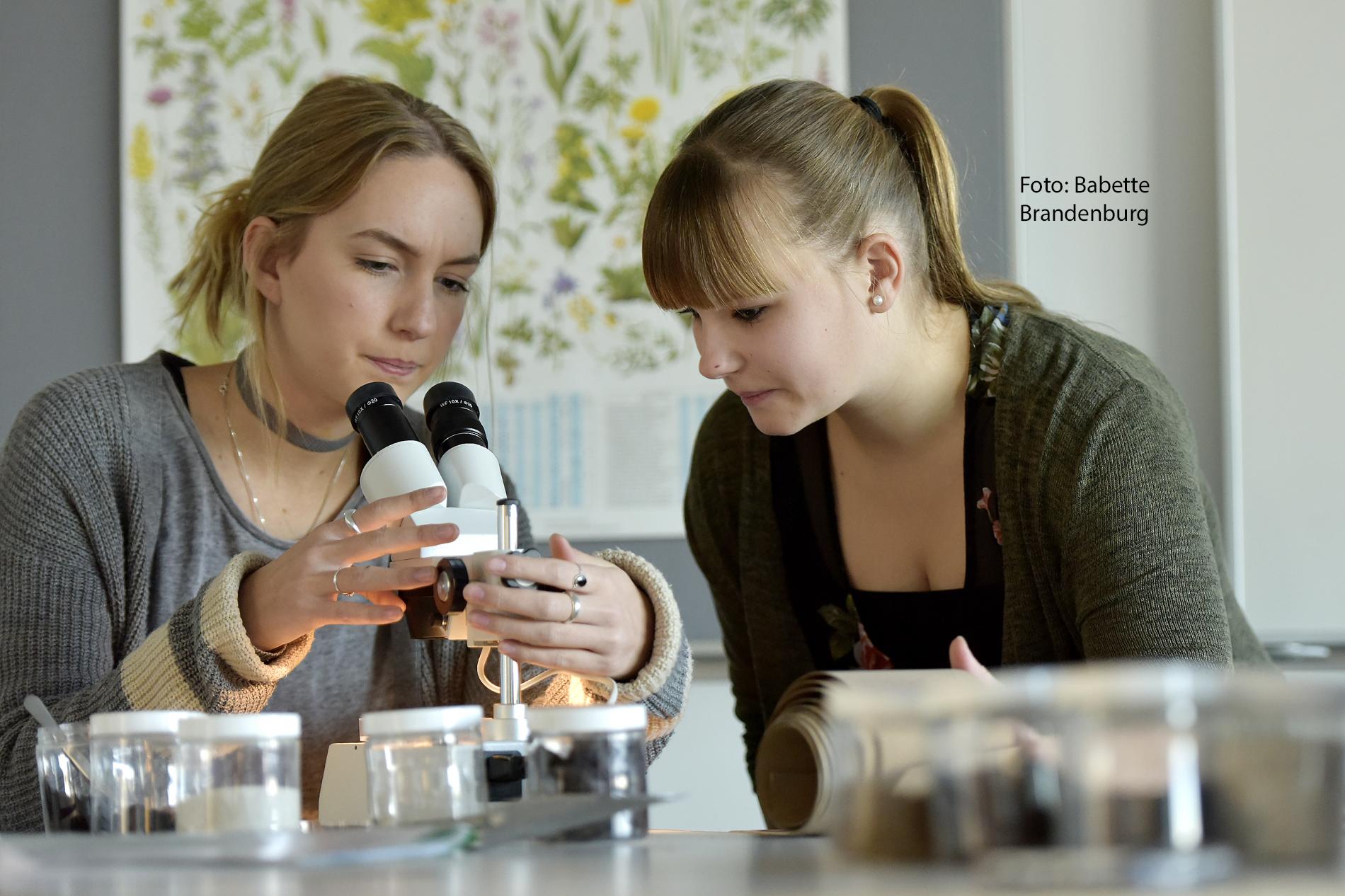 Das Bild zeigt 2 sitzende junge Frauen an einem Mikroskop