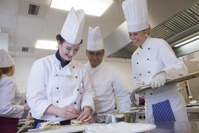 2 auszubildende Köche mit Ausbilder stellen eine Speise her