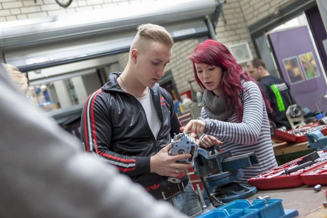 ein junger Mann und eine junge Frau betrachten an einer Werkbank ein technisches Gerät