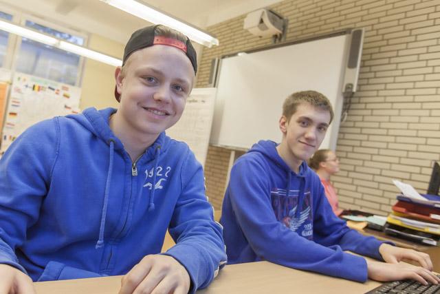 das Bild zeigt zwei junge Männer an einem Schulschreibtisch sitzen Männer in