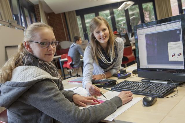 das Bild zeigt zwei junge Frauen am Schreibtisch mit PC