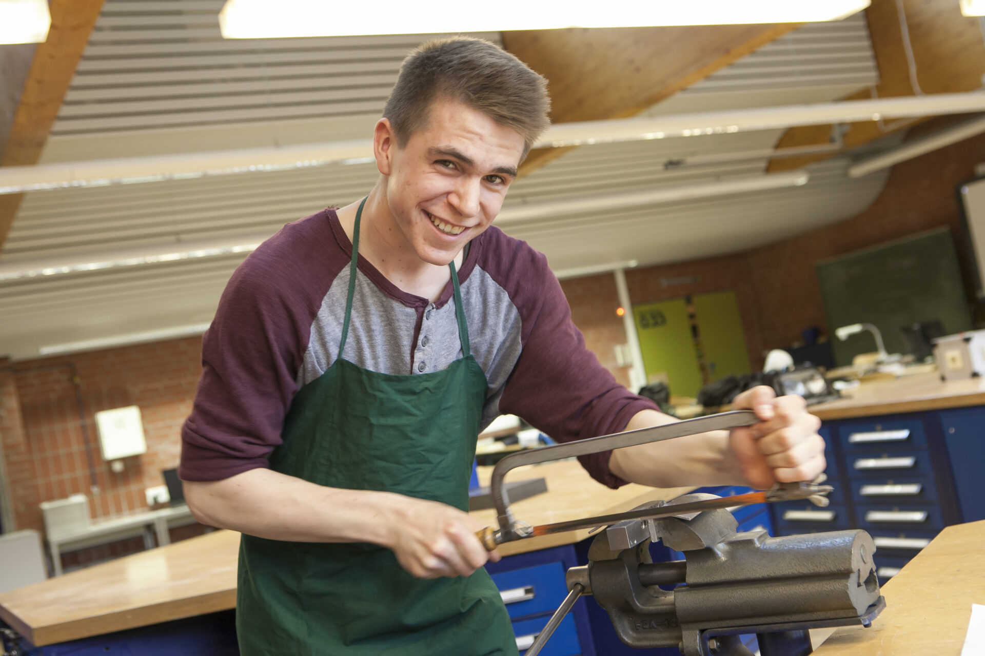 das Bild zeigt einen jungen Mann an einer Werkbank mit einer Handsäge