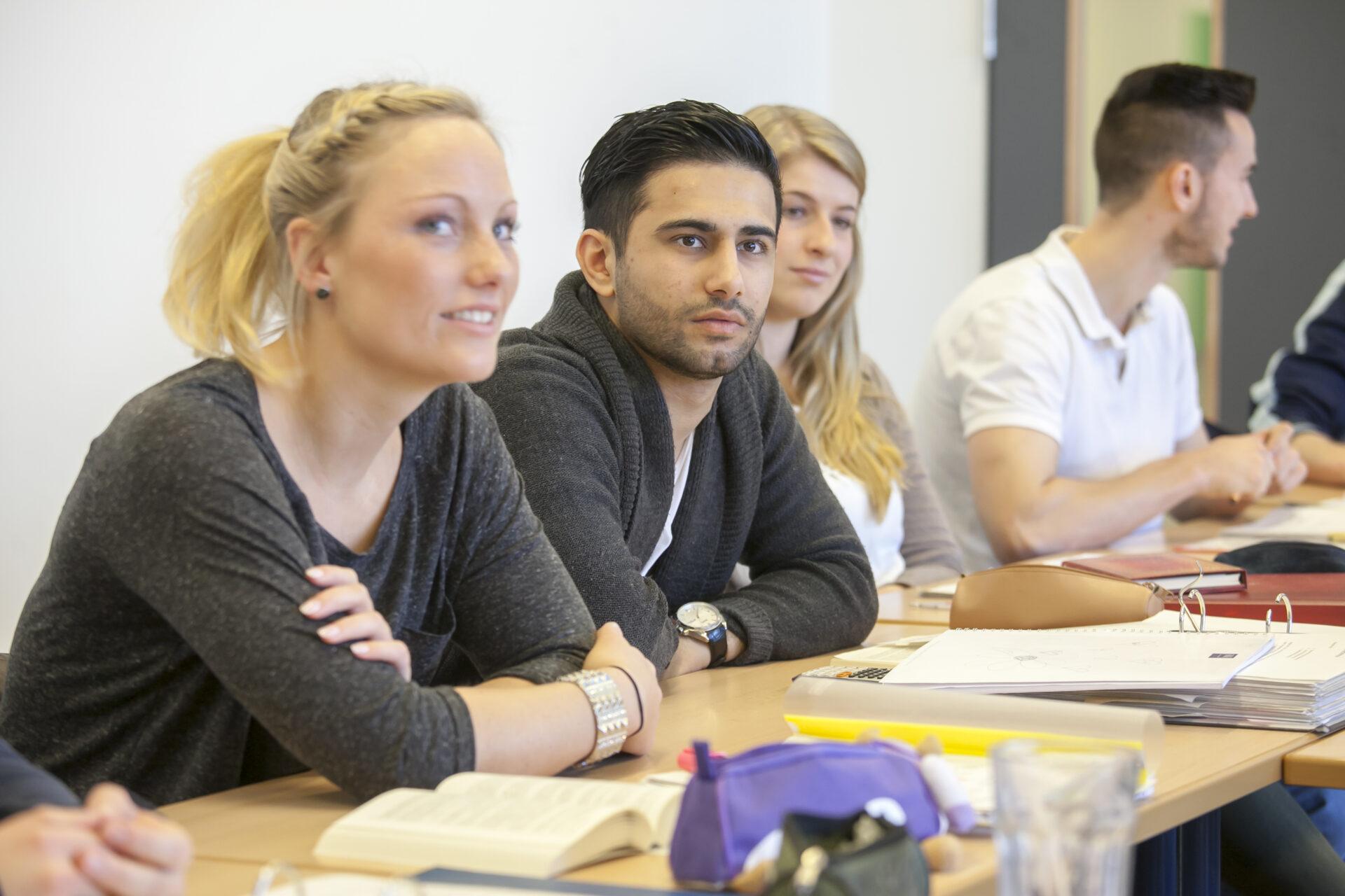 das Bild zeigt vier junge Menschen, davon eine junge Frau und einen jungen Mann im Vordergrund, an Schultischen sitzen