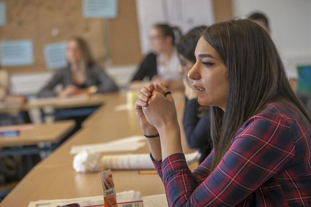 das Bild zeigt eine junge Frau in einer Schulklasse am Schreibtisch sitzend