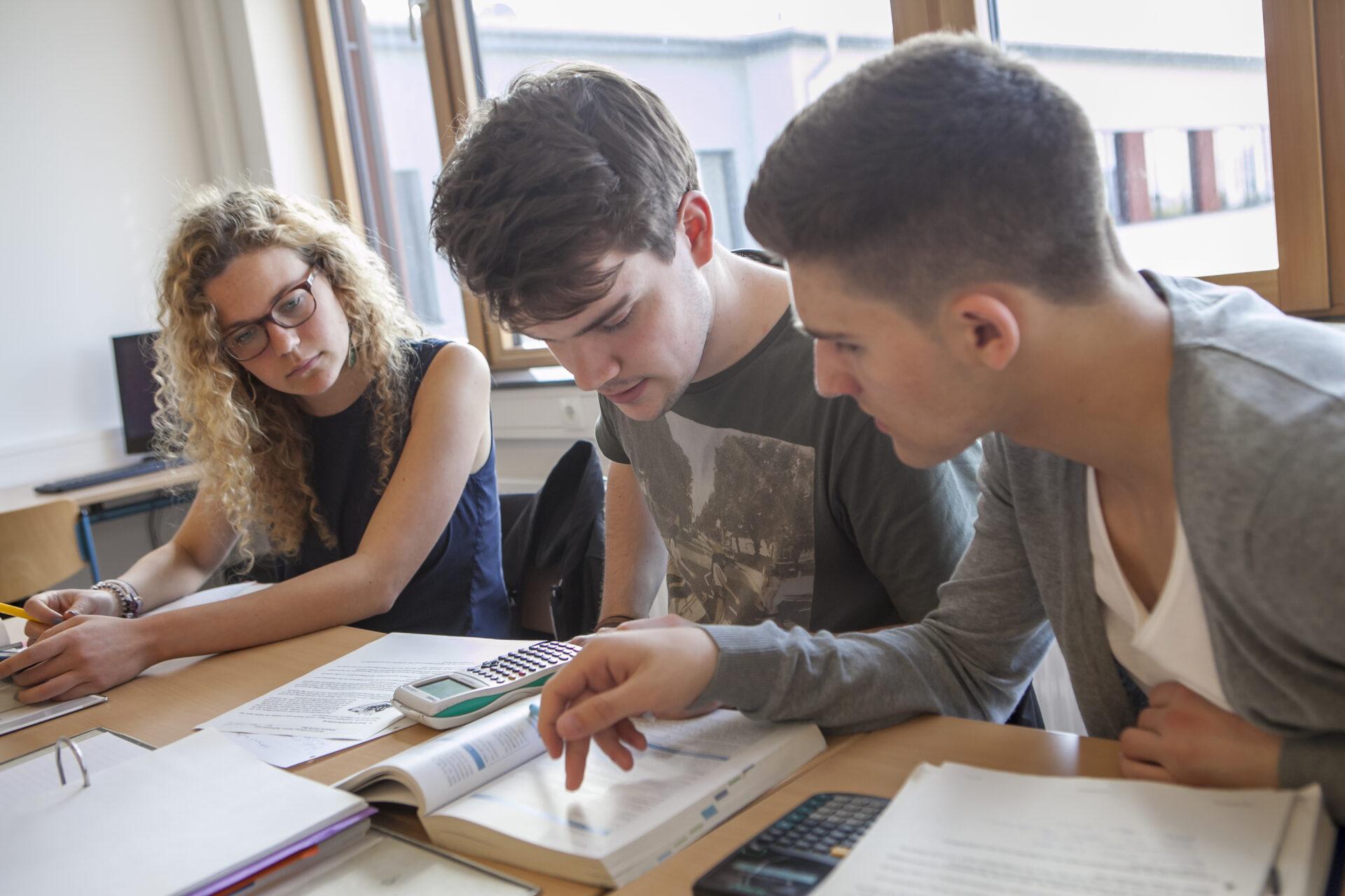 das oto zeigt eine Schülerin und zwei Schüler gemeinsam an einen Tisch sitzen und in einem Buch lesen