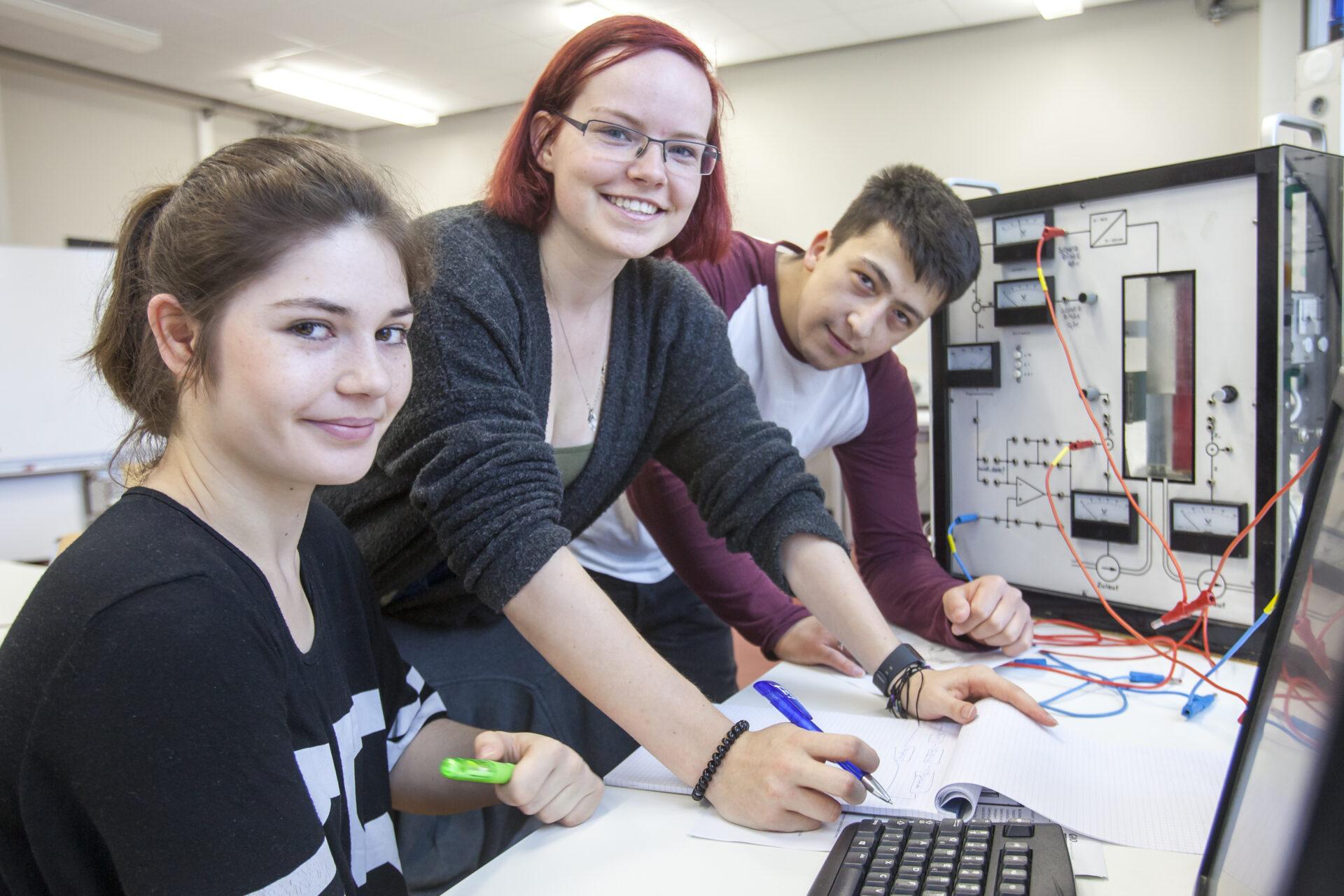 Drei junge Menschen arbeiten mit einem elektronischen Gerät