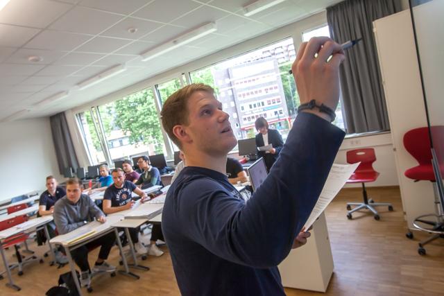 das Bild zeigt einen jungen Mann vor einer Berufsschulklasse, der einen Stift in der Hand hat