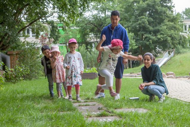 Das Bild zeigt 4 spielende Kinder auf einen Rasen vor 2 Betreuern, einen Mann und einer Frau