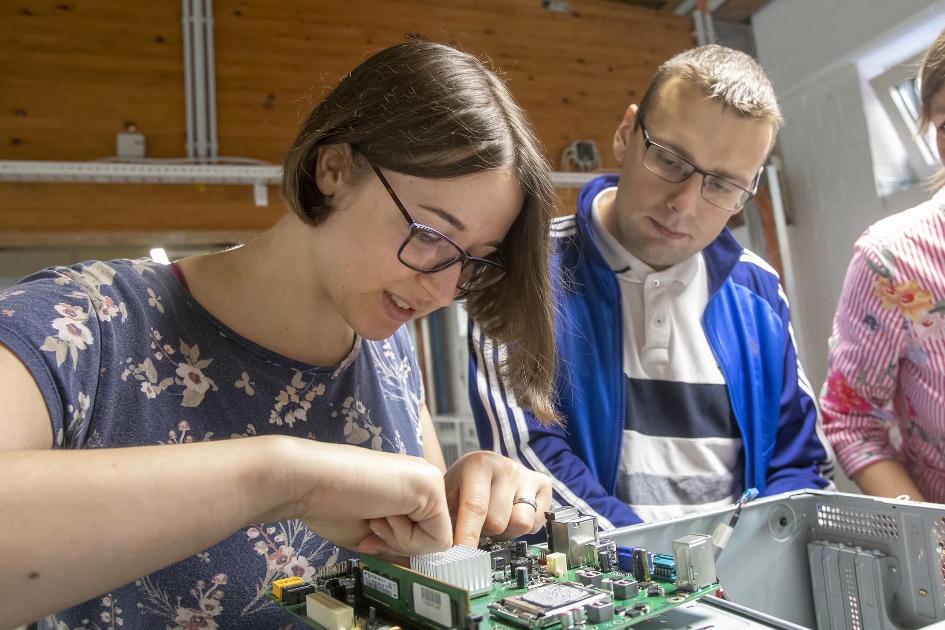 das Foto zeigt eine junge Frau, die an technischen Inneren eines PC arbeitet. Ein junger Mann daneben schaut zu