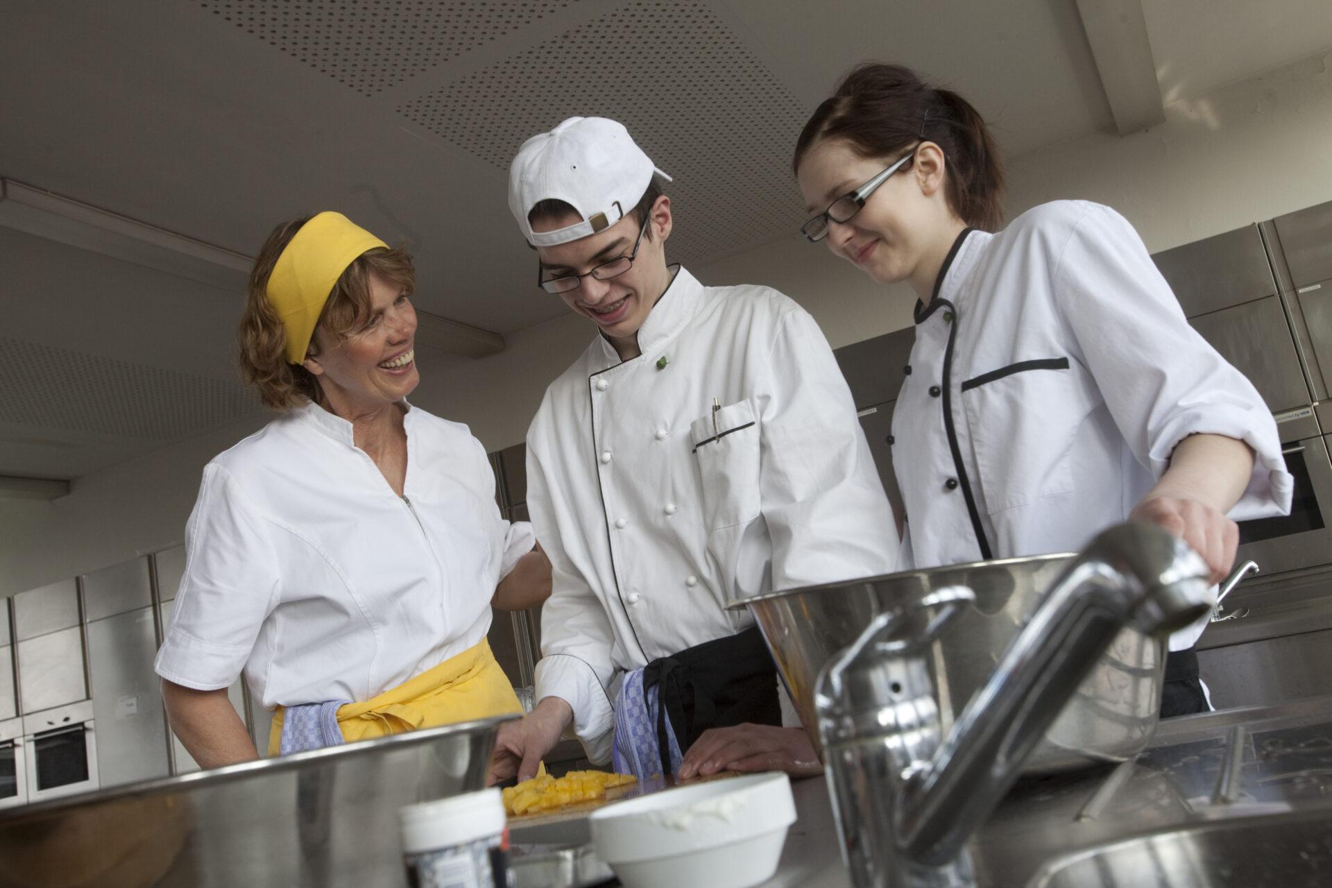 das Bild zeigt 2 Frauen und einen jungen Mann in einer Lehrküche